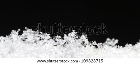 Small white background with black snow crystals in the black winter panorama - stock photo