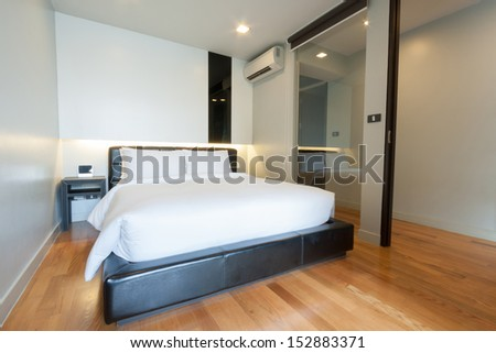 small white bedroom in apartment.