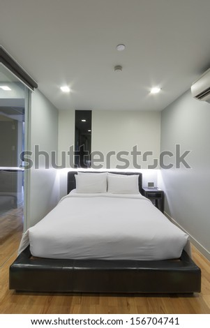 small white bedroom in apartment. - stock photo