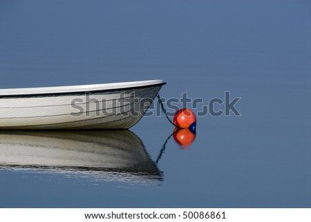 Small white boat on a perfectly still calm blue water surface. - stock photo