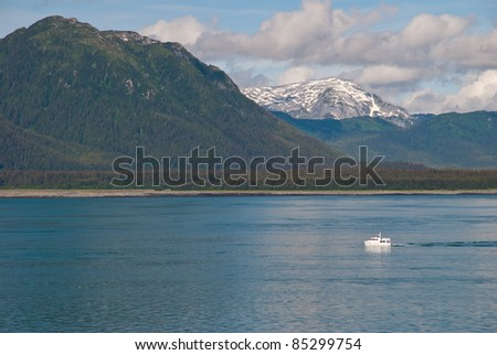 Small white boat sailing in the sea with tall majestic mountains in background. - stock photo