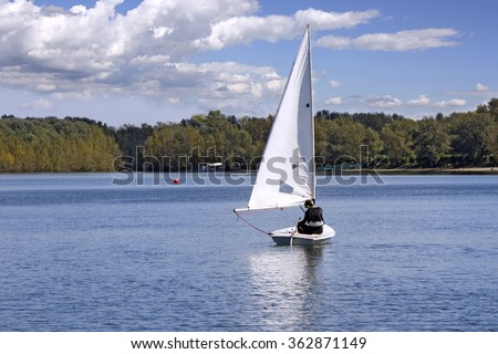 Small white boat sailing on the lake  - stock photo