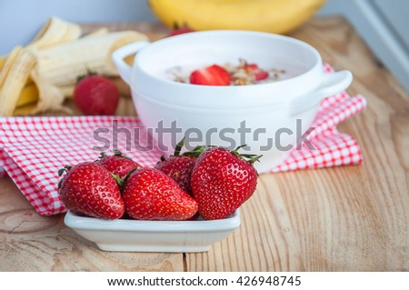 Small white bowl filled with fresh ripe red strawberries and bananas on an old wooden textured table with red fabric - stock photo