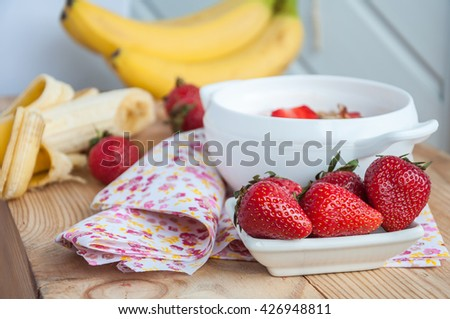 Small white bowl filled with fresh ripe red strawberries and bananas on an old wooden textured table with flower fabric - stock photo