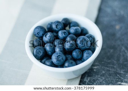 Small white bowl of blueberries on linen tablecloth close up - stock photo