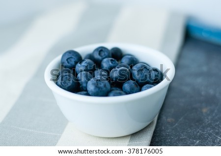 Small white bowl of blueberries on linen tablecloth close up, side view - stock photo