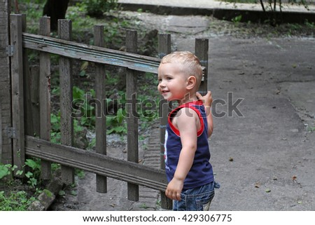 Small white boy opens an old wooden gate and smiles. For the child, opened the road to a successful future. - stock photo