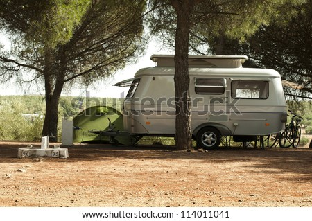 Small white caravan through the trees. Green tent and bikes. - stock photo