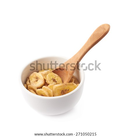 Small white ceramic bowl filled with the dried banana slices and wooden measuring spoon, composition isolated over the white background - stock photo