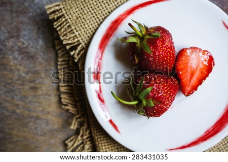 Small white china bowl filled with succulent juicy fresh ripe red strawberries on an old wooden textured table top - stock photo