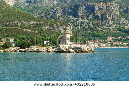 Small white church on the island, blue Mediterranean sea and high mountains in the background