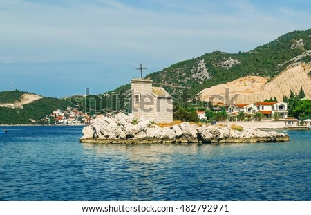 Small white church on the island in Klek, Croatia, Adriatic sea and high mountains in the background