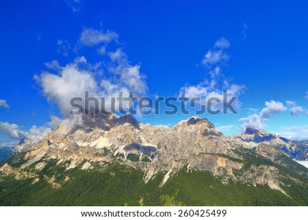 Small white clouds on top of Monte Cristallo seen across by green valley from Cadini di Misurina, Dolomite Alps, Italy - stock photo