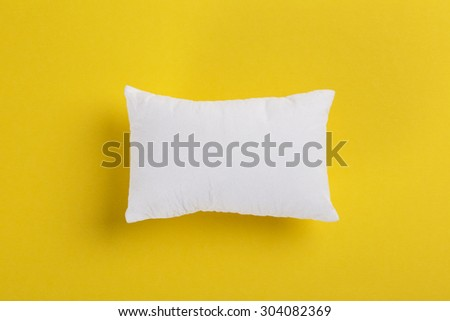 Small white cushion on yellow background, sleep concept, copy space - stock photo