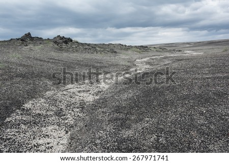 Small white dry river crosses a volcanic soil made by small black stones and disappears over the horizon coinciding with a gray cloudy sky - stock photo
