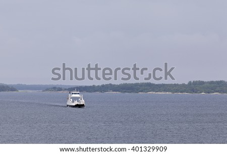 Small white ferry on the route through the archipelago. Islands in the background. Overcast.