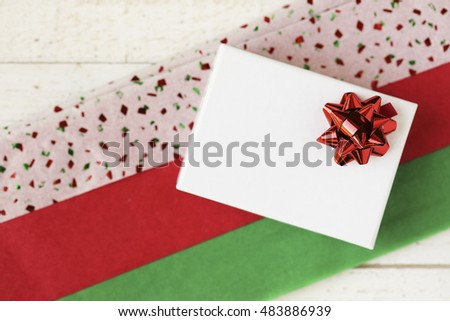 Small white gift box with red bow on colorful red and green tissue paper.