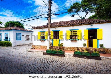 Small white houses with colorful window shutters in Buzios, Brazil - stock photo