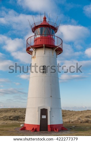 Small white lighthouse on a hill with beach grass on Sylt island, Germany - stock photo