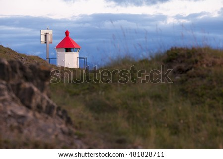Small white lighthouse with solar panel at rocks at Helgeland coast, Norway.