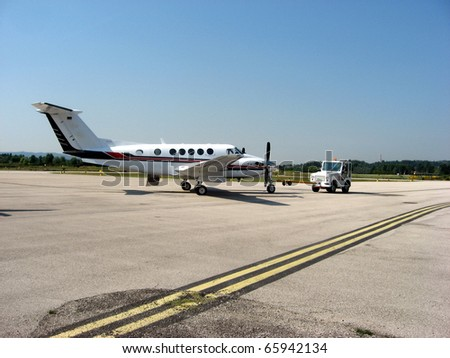 small white plane in the airport is ready for takeoff on runway - stock photo