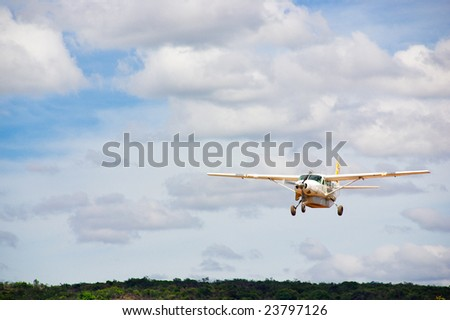 Small white plane with propeller in cloudy sky over jungle