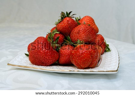 Small white plate, filled with succulent juicy fresh ripe red strawberries on a white textured table - stock photo