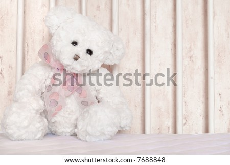 Small white teddy bear, sitting in child cot - stock photo