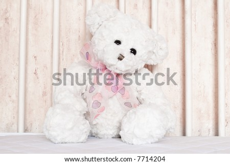 Small, white teddy bear sitting in the center of cot. - stock photo