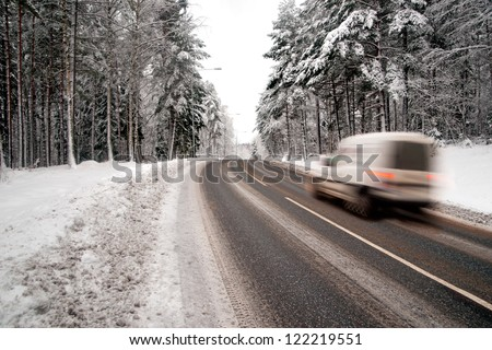 Small white van in blurred motion on country road in winter