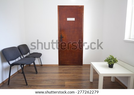 Small white waiting room without people. A doctor, dentist or other medical practitioner provides this room for the use of people who are waiting to be seen.  - stock photo