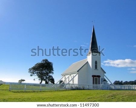 small white wooden protestant church with a blue sky - stock photo