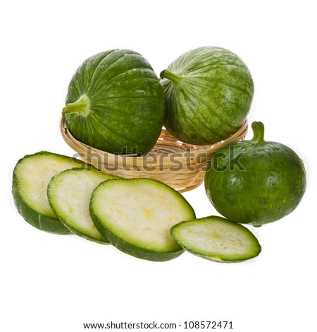 small whole round zucchini in a wicker basket and a number of sliced circles isolated on white backgroun - stock photo