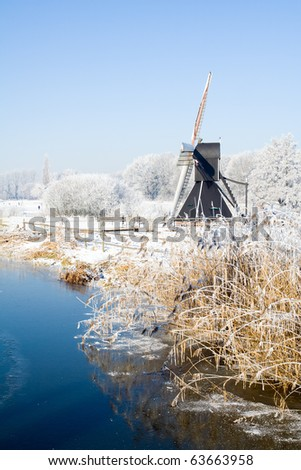 Small windmill next to a river on a cold winter day - stock photo