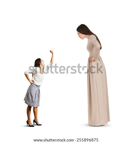 small woman screaming and showing fist to big serious woman over white background - stock photo