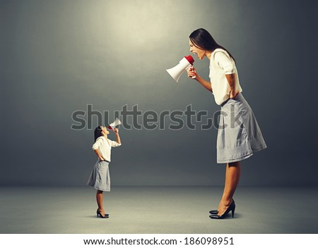 small woman screaming at big displeased woman over dark background - stock photo