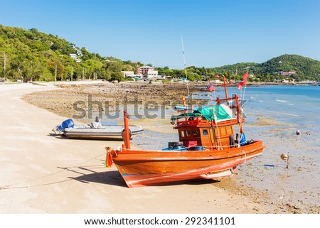 small wood fishing boat on sichang beach from Thailand - stock photo