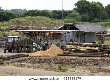 Small wood mill station with tractor. - stock photo