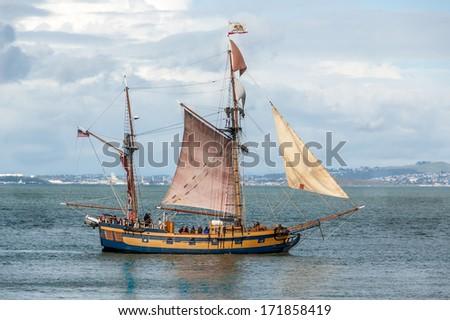 Small wood sailing ship plys waters in San Francisco Bay, California. - stock photo