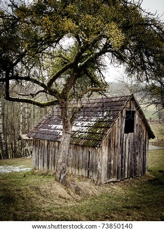 Small wooden Barn with a tree in Winter - stock photo