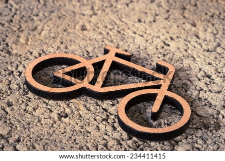 Small wooden bicycle on the road, soft focus - stock photo