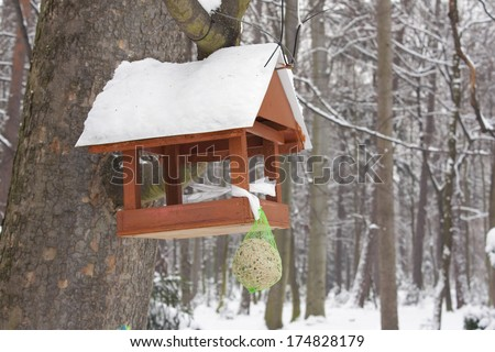 Small wooden bird house hanging on a tree covered in snow. - stock photo