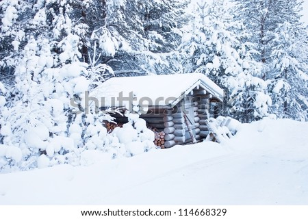 Small wooden blockhouse in the twilight, in winter under the snow in the snowy forest of pine trees, winter landscape - stock photo