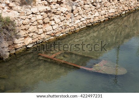 Small wooden Boat under the water, sunk boat in the channel, near the wall