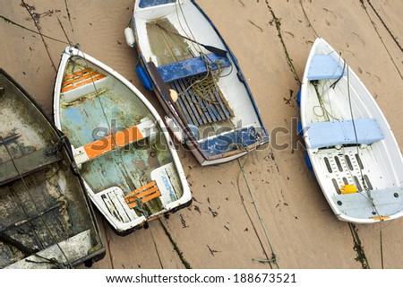 Small wooden boats beached high and dry on the sand by the retreating tide in St Ives harbour in Cornwall a popular fishing village and tourist resort - stock photo