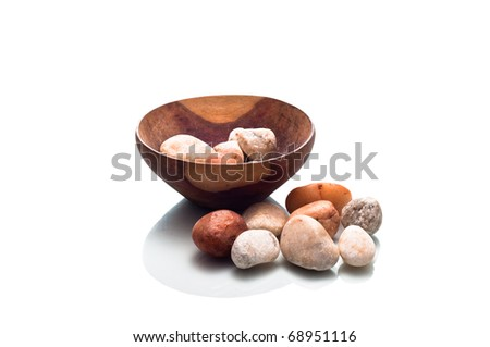 Small wooden bowl containing stones isolated on a white background - stock photo