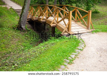 Small wooden bridge and walking lane in park, Trigorskoye village, Russia - stock photo
