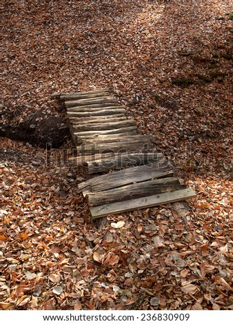 small wooden bridge on a background of yellow fallen leaves - stock photo