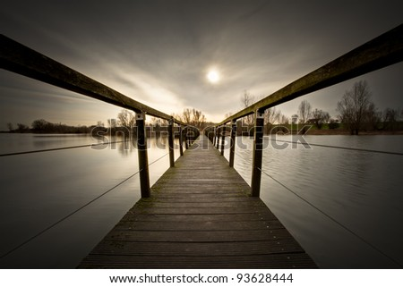 Small wooden bridge over flooded river. - stock photo
