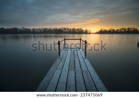 small wooden bridge over the river,river in winter - stock photo